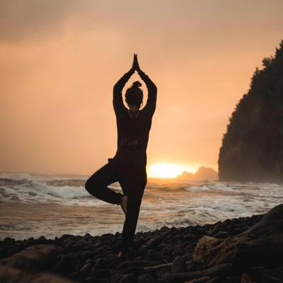 Eine Frau macht am Strand Yoga.